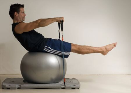 muscled: Young athletic man doing Pilates on a balance ball. Isolated against a gray studio background
