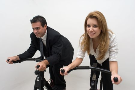 Young business colleagues riding on exercise bikes together. Horizontally framed shot with both subjects facing forward. Isolated.