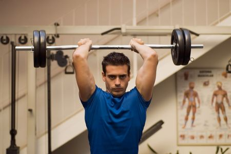 Attractive, athletic man lifting weights in a gym.
