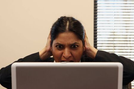 deletes: Businesswoman touching her head in shock as she accidentally deletes a file from her laptop. Stock Photo