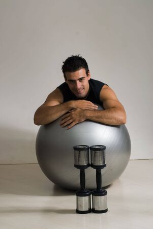 Attractive male personal trainer smiling while leaning on a balance ball. Isolated.
