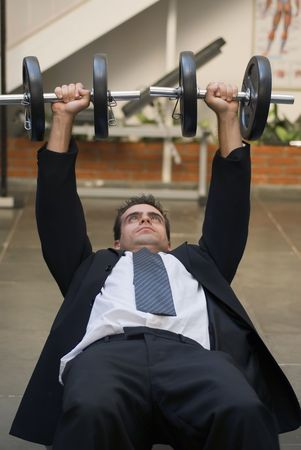 Vertically framed shot of an athletic, young businessman bench pressing weights in a gym