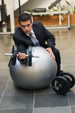 Attractive young executive doing biceps curls in a gym, dressed in a business suit. Stock Photo