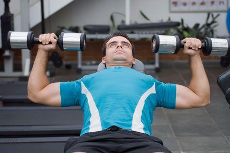 Male athlete doing a dumbbell bench press. Banco de Imagens
