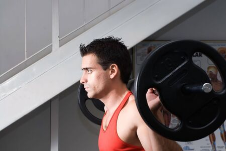 male athlete: Male athlete doing squats with a barbell.