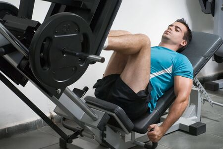 Male weightlifter doing leg presses. Stock Photo