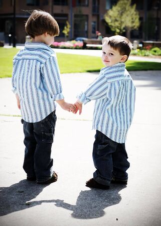 Two identically dressed brothers holding hands in a park. High-contrast style