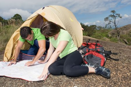 Young couple checking their route on a map in front of their tent with ominous gray clouds gathering overhead. Horizontally framed shot. photo