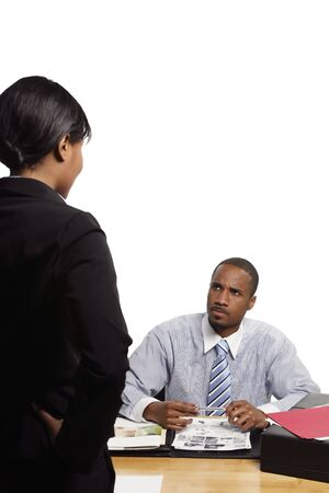Seated boss looking angry as a female subordinate gives him some news. Vertical shot isolated on white Stock Photo