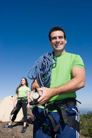 Attractive young man with climbing gear showing off his compass with an attractive woman in the background. Couple is enjoying a camping trip together. photo