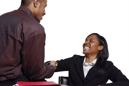 businessmen shaking hands: Male and female business colleagues smiling broadly and shaking hands