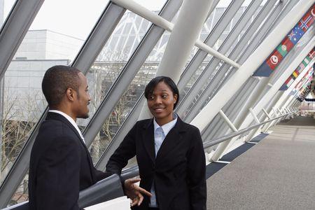 オフィスのロビーでミーティングを持つ男性および女性実業家