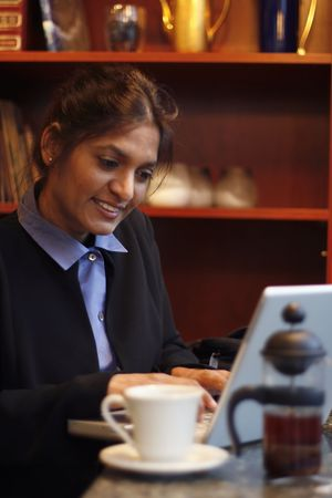 Businesswoman working on a laptop in a cafe. Vertically framed shot. photo