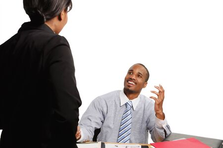 subordinate: Seated boss smiling broadly as a subordinate delivers some news. Isolated on white. Stock Photo