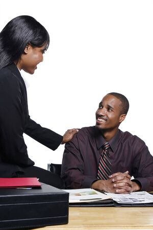 Male and female colleagues sharing a quiet moment. She is sitting on his desk and has a hand on his shoulder comforting him Stock Photo