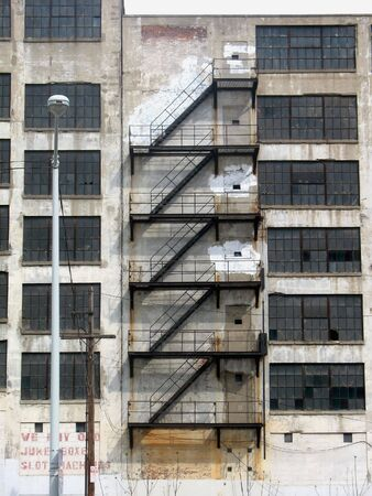 Fire escape stairs snaking down the outside of an old abandoned building
