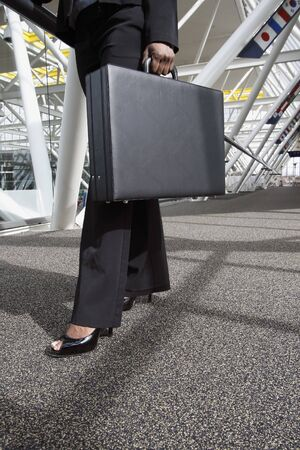 Close up of a businesswomans legs and briefcase as she strides through an office lobby. Vertically framed shot.