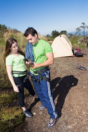 Attractive couple checking out their climbing gear while on a camping trip photo