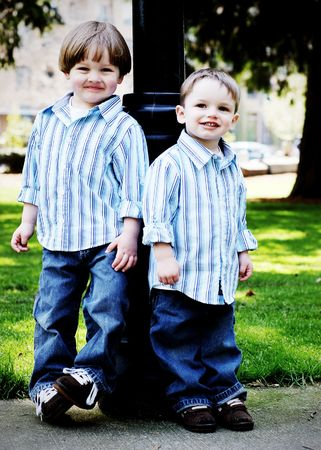 Two brothers dressed identically in a striped shirt and blue jeans standing shoulder to shoulder in a park. High-key style, vertically-framed shot.