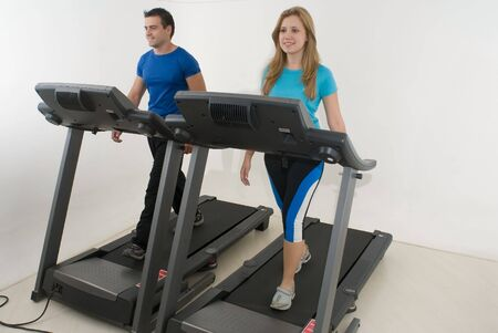 Attractive young couple working out together at the gym on treadmills. Horizontally framed shot with the couple facing directly ahead