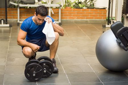 Male athlete kneeling down by dumbbells toweling sweat of his brow.