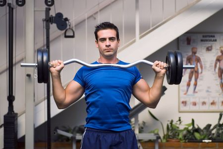 Male weightlifter, looking straight into camera, holding barbell weights. photo