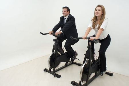 Two business colleagues on exercise bikes. They are dressed in business suits and facing straight ahead. Horizontally framed shot. Stock Photo