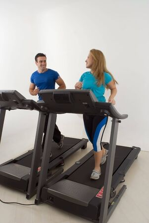 muscled: Attractive young couple working out together at the gym on treadmills. Vertically framed shot