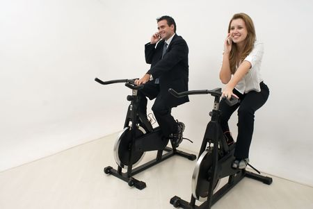 Businessman and businesswoman dressed in suits riding on exercise bikes and chatting on their cellphones