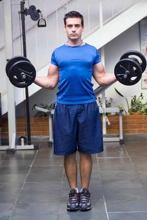 exerting: Male athelete  weightlifter, looking straight into camera, doing curls with dumbbell weights in his hands.