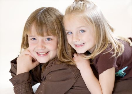 Two cute young sisters posing together in a studio. Horizontally framed shot isolated against a white studio background.