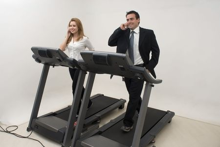 Two businesspeople (male and female) running on a treadmill and talking on their cell phones photo