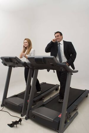 Male and female businesspeople jogging on a treadmill while talking on their phones photo