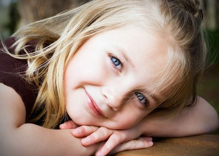 Cute blond girl resting her head on her arms smiling at the camera