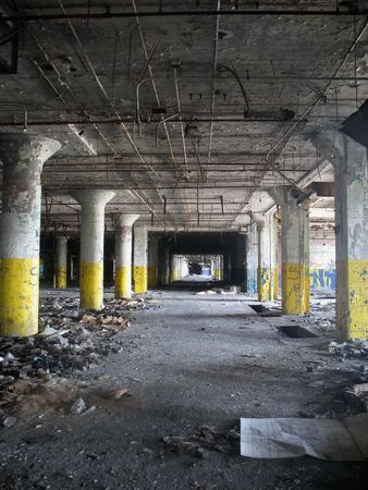 An indoor vertical shot of an abandoned factory  warehouse, with a single vanshing point.