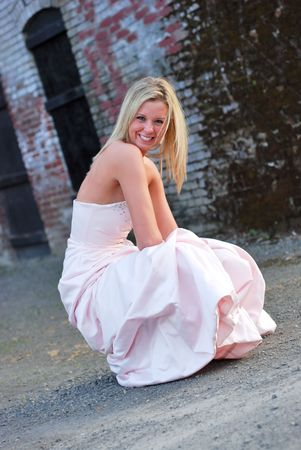 centering: Vertically framed outdoor shot a smiling attractive bridesmaid crouching down in unpaved lot in front of red brick wall.
