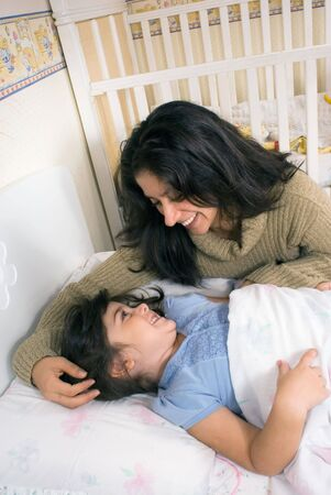 Mother tucking her adorable daughter in for the night Stock Photo - 3116469