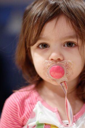 Cute giovane ragazza con un pacificare nella sua bocca. Verticalmente incorniciata vicino coltivati tiro.