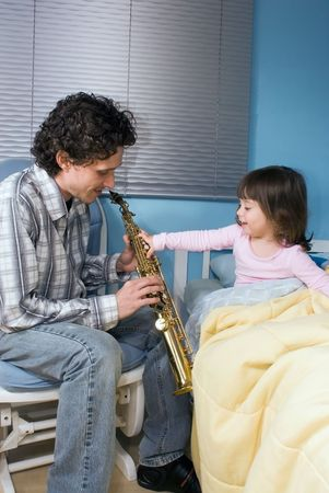 lullaby: Little girl reaching out to grab her fathers saxophone while he plays her a lullaby