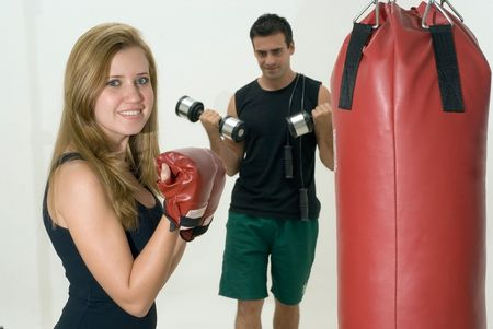 Isolated shot of an attractive man and woman exercising together.  The man is curling dumbbells and the woman is boxing a heavy bag while looking at the camera. photo