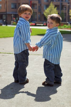 Outdoors shot of two young brothers holding hands looking back at the camera, wearing identical button-up shirts and blue jeans.