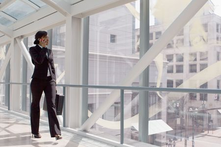 Horizontal shot of a businesswoman, talking on a cellphone, walking through a skybridge Stock Photo - 3116435