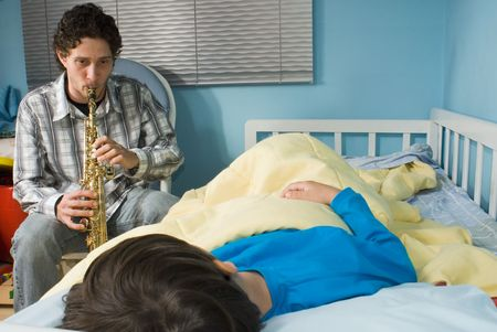 gets: Young father playing a tune on a saxophone as his son gets ready to fall asleep