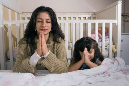 Mother and daughter saying their prayers together before going to bed photo