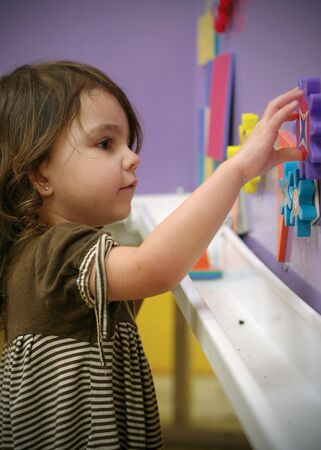 Cute young girl playing with educational toys at school. Vertically framed shot