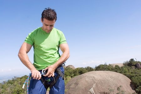 Athletic young man attaching a climbing rope to his climbing harness.  Stock Photo
