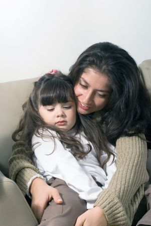Mother whispering to her sleepy daughter as she falls asleep in her lap photo