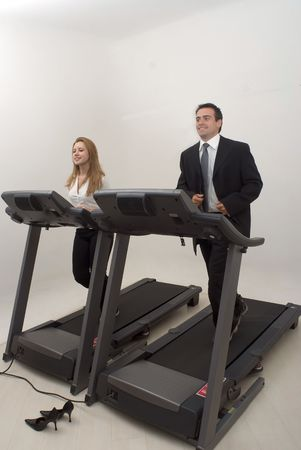 Male and female business colleagues on a treadmill together. Isolated against a studio background Stock Photo