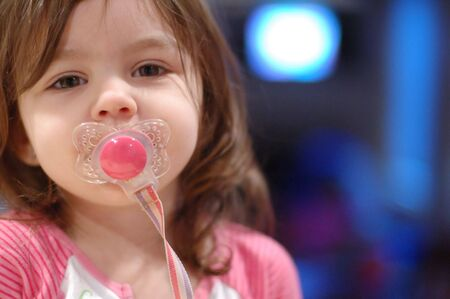 Cute young girl with a pacifier in her mouth. Horizontally framed close-cropped shot.
