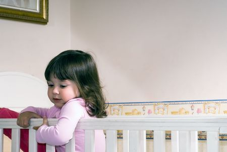 Adorable young girl climbing around the guardrail of a bedroom crib